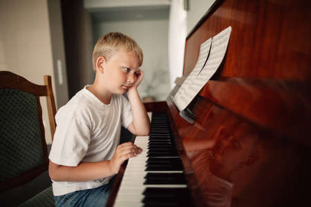 little funny boy plays piano at home