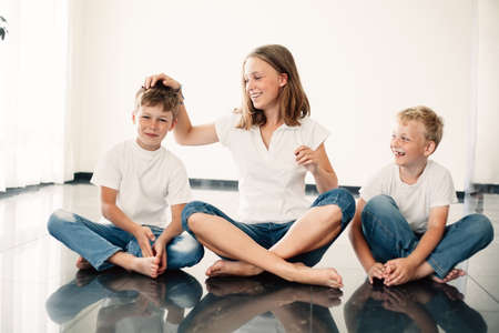 photo of young girl with brothers at home