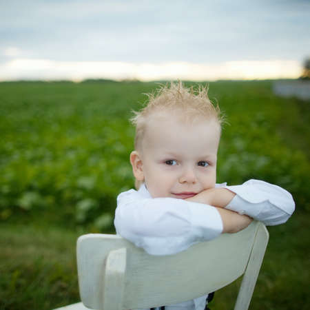 sits on a chair: little boy sits on chair in the field