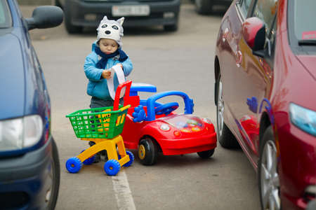 shopping carriage: little boy on supermarket parking with shopping carriage