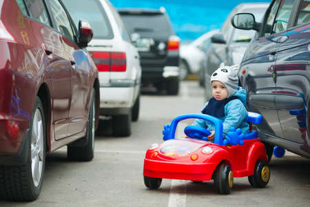 photi of cute little boy on supermarket parking Stockfoto