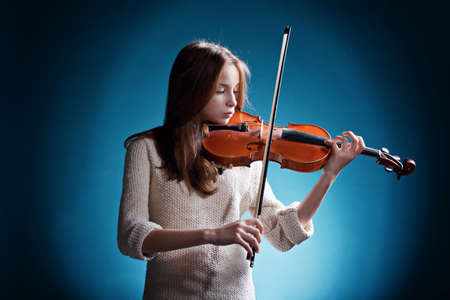 photo of young beautiful girl plays on violin
