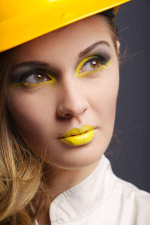 yellow helmet: Beautiful girl with yellow helmet studio portrait