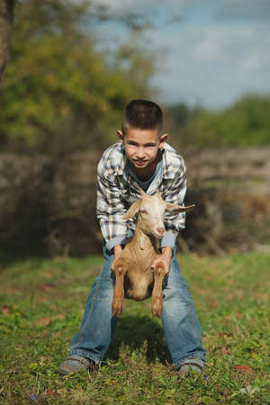 two stroke: cute little boy with goat on the farm