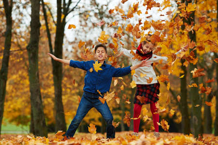 kids jumping: boy and girl among the leaves in autumn park Stock Photo