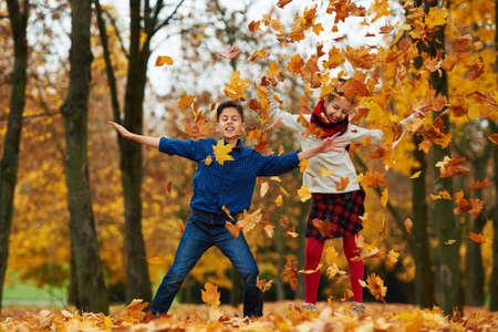 gente saltando: ni�o y ni�a entre las hojas en el oto�o de parque