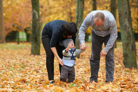 disguised: mom and dad disguised child in autumn park Stock Photo