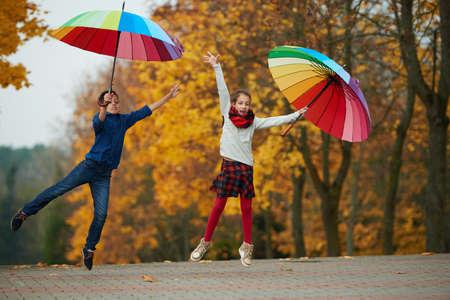 niño saltando: niño y niña entre las hojas en el otoño de parque