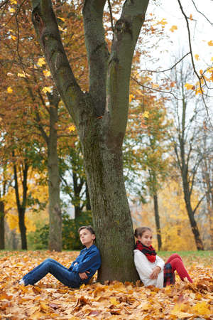 strife: boy and girl among the leaves in autumn park Stock Photo