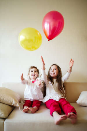 children celebration: two girls playing with balloons at home