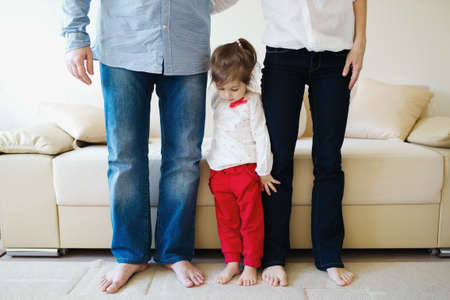 hugging legs: little girl hugging mom and dad for legs