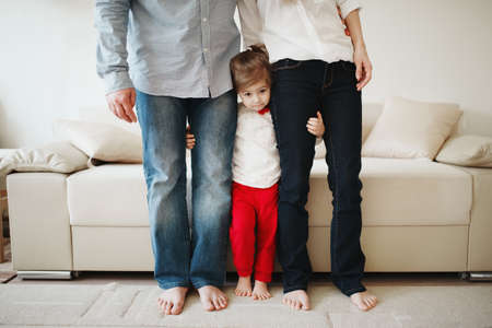 man woman hugging: little girl hugging mom and dad for legs