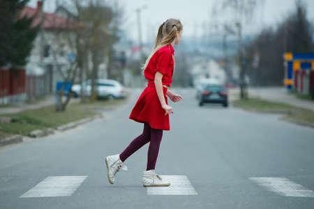 paso peatonal: foto de ni�a de cruzar la calle en el cruce de peatones Foto de archivo