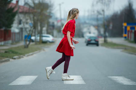 photo of girl crossing street on the crosswalk