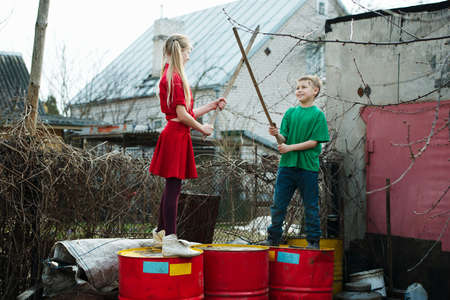 children play: children play at dump drums of oil Stock Photo