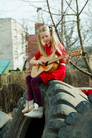 landfill: girl playing guitar sitting on tires in landfill Stock Photo