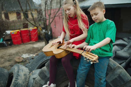 children play: happy children learn to play the guitar
