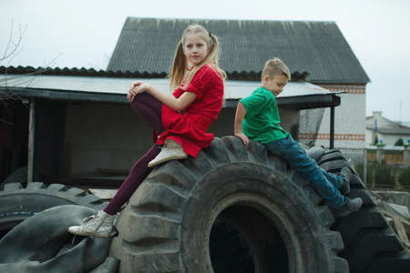 junkyard: photo of happy children playing in junkyard tires Stock Photo