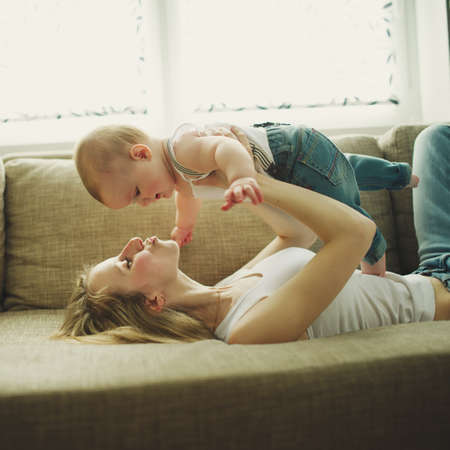 a young baby: beautiful young mother with baby at home