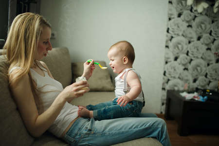 crying baby: young mother feeding baby with a spoon
