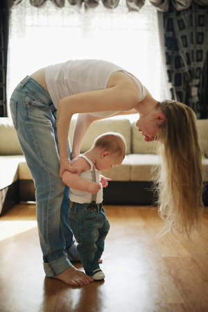a young baby: young beautiful mother teaches baby to walk
