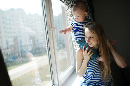 a young baby: young mother with baby at the window