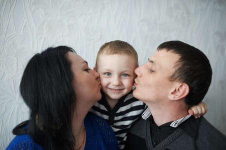 mom: mom and dad kiss son at home Stock Photo