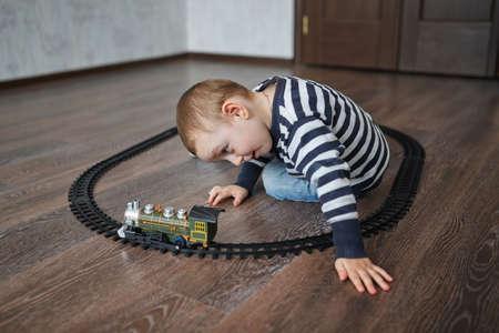 kinder spielen: Foto des kleinen glücklichen Jungen baut Spielzeug-Eisenbahn
