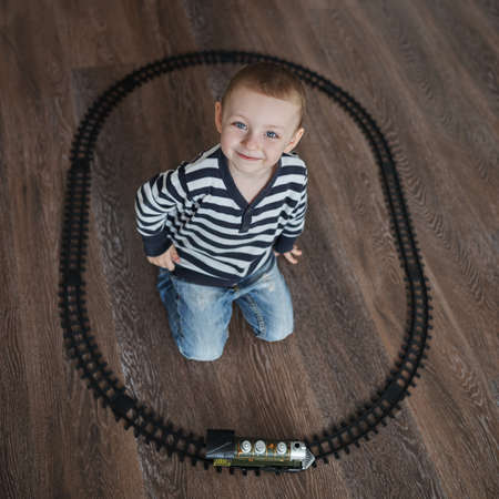 builds: photo of little happy boy builds toy railroad
