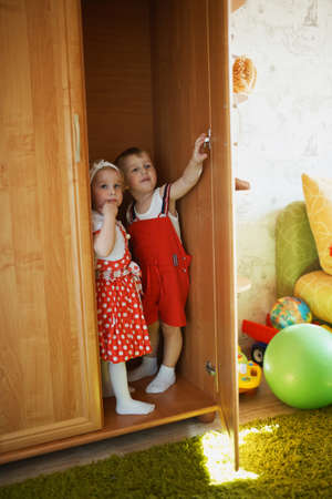 hide and seek: boy and girl playing hide and seek in closet Stock Photo