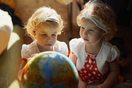 niñas gemelas: dos niñas gemelas lindas que juegan con el globo