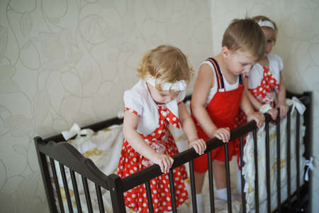 cot: boy with two girls twins in cot