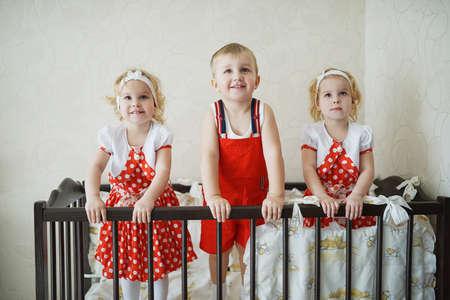 gemelos niÑo y niÑa: niño con dos gemelos niñas en cuna