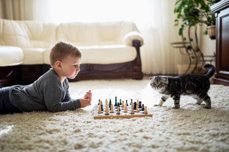 jugando ajedrez: niño juega con el ajedrez gato acostado en el suelo Foto de archivo