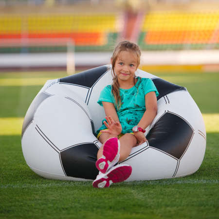 little league: photo of little funny girl on football stadium