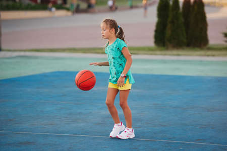 photo of little cute girl playing basketball outdoors Stockfoto