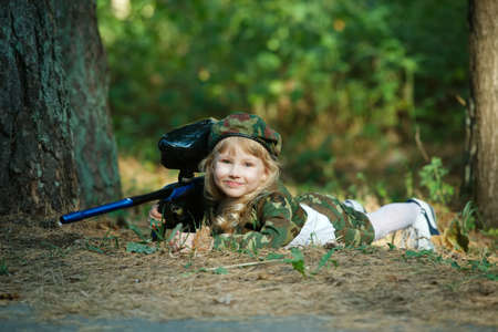 army face: little girl in camouflage suit with rifle