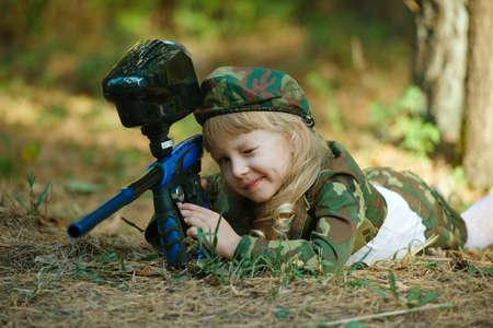 Niña en traje de camuflaje con el rifle Foto de archivo - 47426029