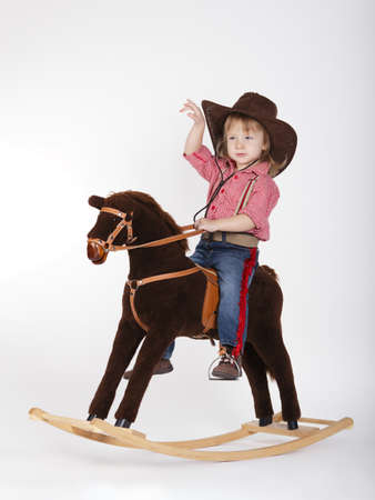 cowgirl hat: little funny cowgirl riding horse on white Stock Photo