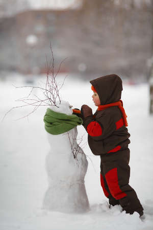 clothes interesting: photo of little cute boy with snowman