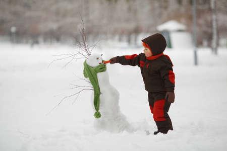 yard stick: photo of little cute boy with snowman