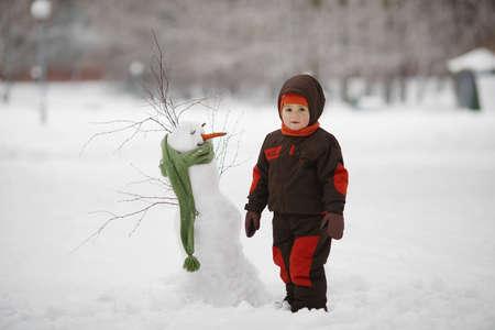 bonhomme de neige: photo de petit gar�on mignon avec bonhomme de neige Banque d'images