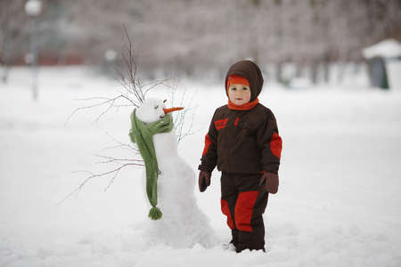 snowman: photo of little cute boy with snowman