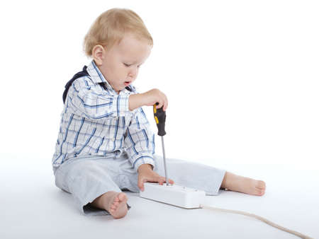 little boy plays with plug and screwdriver Stock Photo