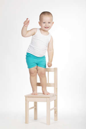 little funny boy on chair on white background