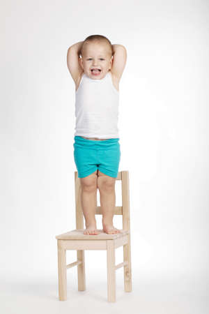 good boy: little funny boy on chair on white background