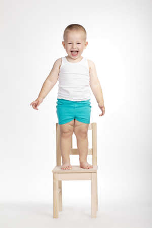 schooler: little funny boy on chair on white background