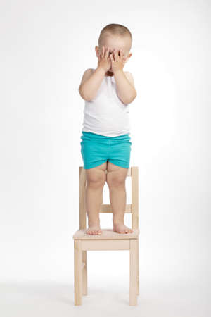 pre schooler: little funny boy on chair on white background