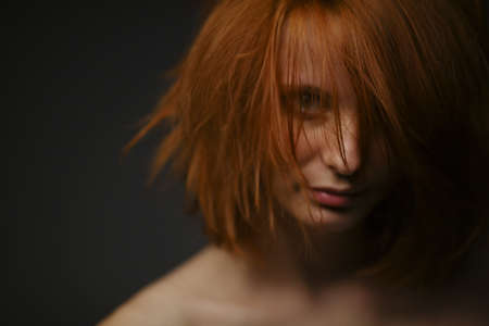 red haired girl: beautiful red haired girl portrait on dark background