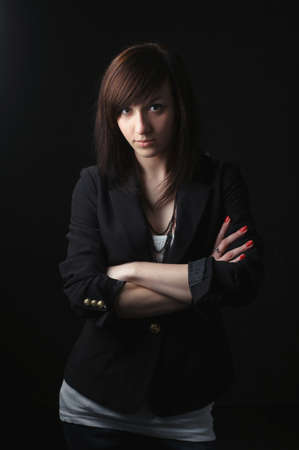 young adult woman: photo of beautiful serious girl on dark background